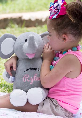 Petite fille disant un secret à sa peluche éléphant brodée et personnalisée